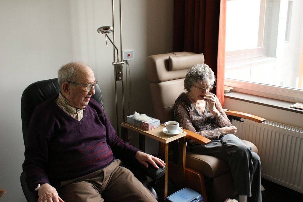 Two elderly people sitting in their chairs