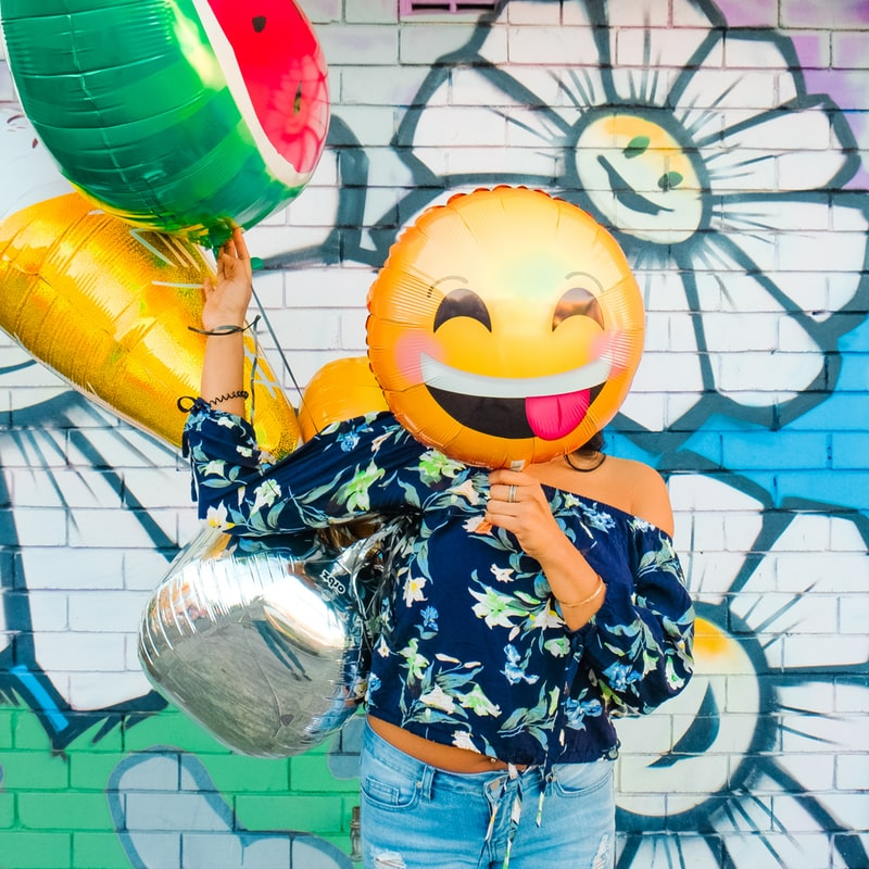 Woman holding emoji balloon